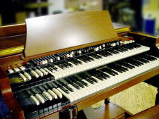 "The Hammond organ, developed by Laurens Hammond and introduced in 1935, was the first commercially successful electric instrument. It was widely used in homes. It was also widely used in jazz, rock, and popular music performance, and it sparked the interest of George Gershwin, Ethel Smith, and other prominant musicians. ---- The original Hammond Organ was Designed and built by the ex-watchmaker Laurens Hammond in April 1935. Hammond set up his 'Hammond Organ Company' in Evanston, Illinois to produce electronic organs for the 'leisure market' and in doing so created one of the most popular and enduring electronic instruments ever built. Hammonds machine was designed using technology that relates directly to Cahill's 'Telharmonium' of 1900, but, on a much smaller scale. The Hammond organ generated sounds in the same way as the Telaharmonium, the tone weel-The tone generator assembly consisted of an AC synchronous motor connected to a geartrain which drove a series of tone wheels, each of which rotated adjacent to a magnet and coil assembly. The number of bumps on each wheel in combination with the rotational speed determined the pitch produced by a particular tone wheel assembly. The pitches approximate even-tempered tuning. The Hammond had a unique drawbar system of additive timbre synthesis (again a development of the Telharmonium) and stable intonation - a perennial problem with electronic instruments of the time. A note on the organ consisted of the fundamental and a number of harmonics, or multiples of that frequency. In the Hammond organ, the fundamental and up to eight harmonics were available and were controlled by means of drawbars and preset keys or buttons. A Hammond console organ included two 61-key manuals; the lower, or Great, and upper, or Swell, and a pedal board consisting of 25 keys. The concert models had a 32-key pedalboard. Hammond also patented an electromechanical reverb device using the helical tortion of a coiled spring, widely copied in later electronic instruments. As well as being a succesful home entertainment instrument, The Hammond Organ became popular with Jazz, Blues and Rock musicians up until the late 1960's and was also used by 'serious' musicians such as Karheinz Stockhausen in ""Mikrophonie II"""